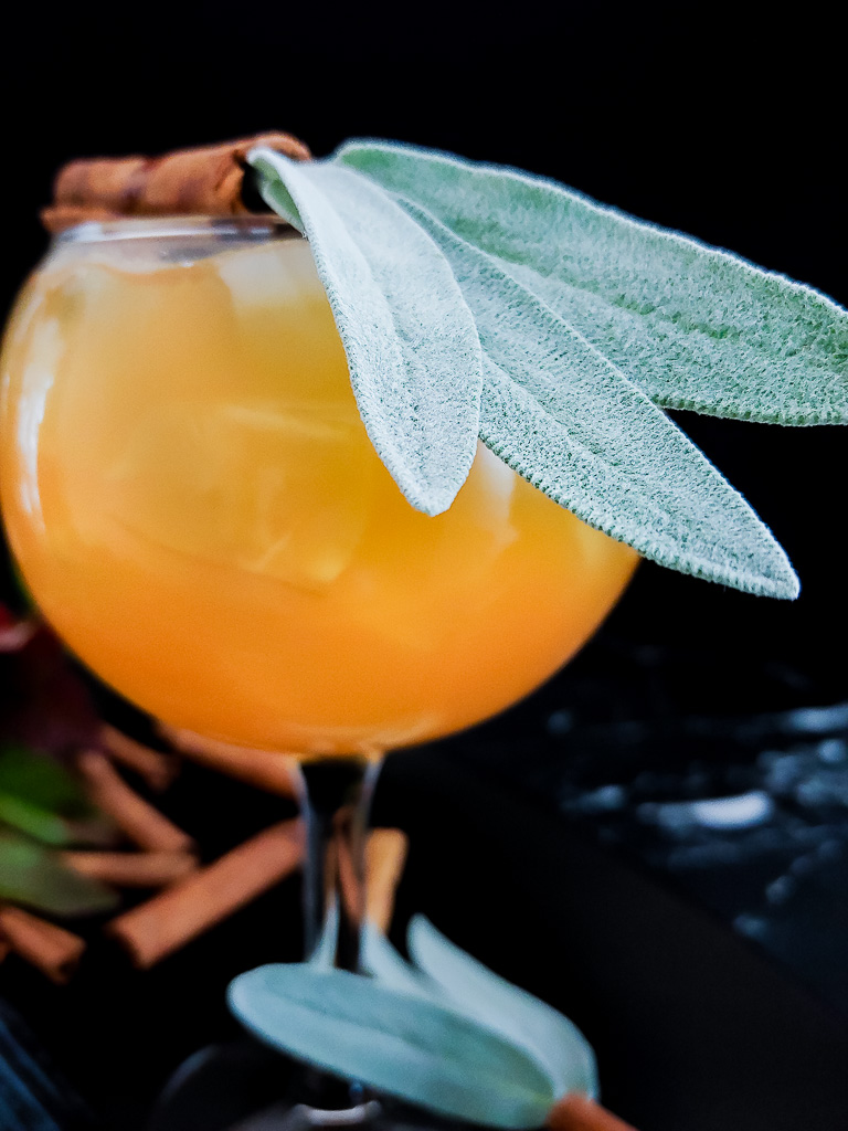 Core Values: Apple Bourbon Cocktail with sage leaf and cinnamon stick garnish
