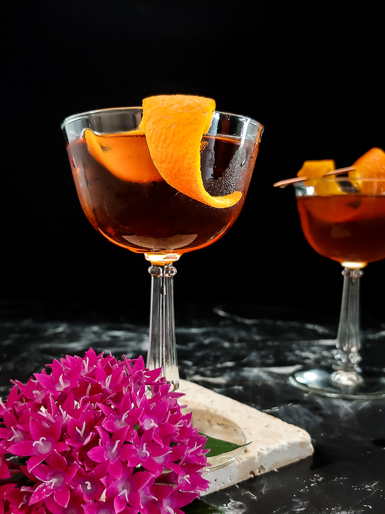 classic manhattan cocktail in a coupe with an orange garnish