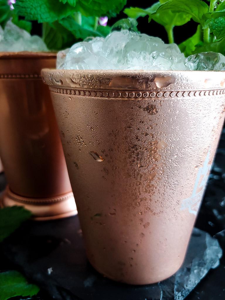 three mint juleps in copper julep cups