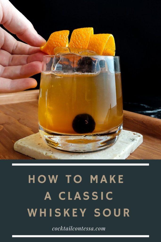 placing orange garnish on a classic whiskey sour