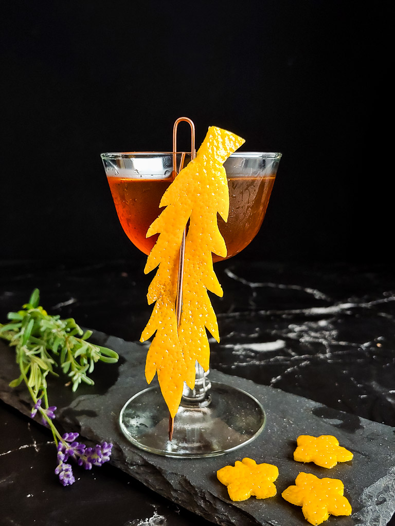 barrel proof manhattan cocktail in a coupe with an orange peel garnish