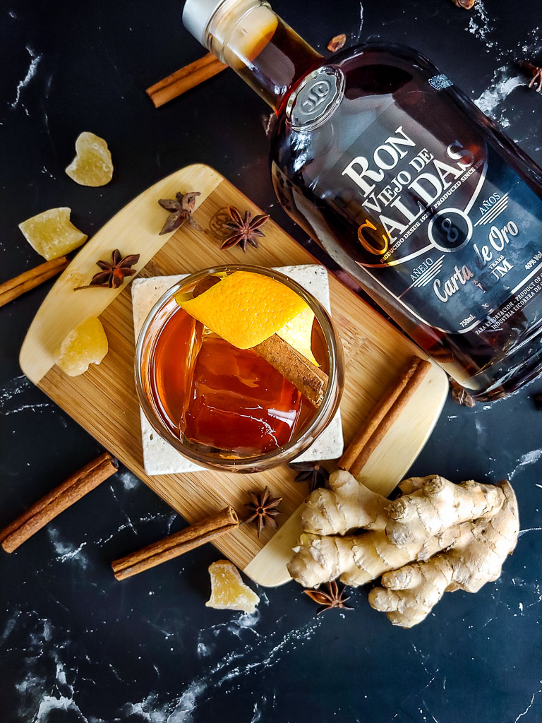rum old fashioned on a cutting board with spices and bottle of rum