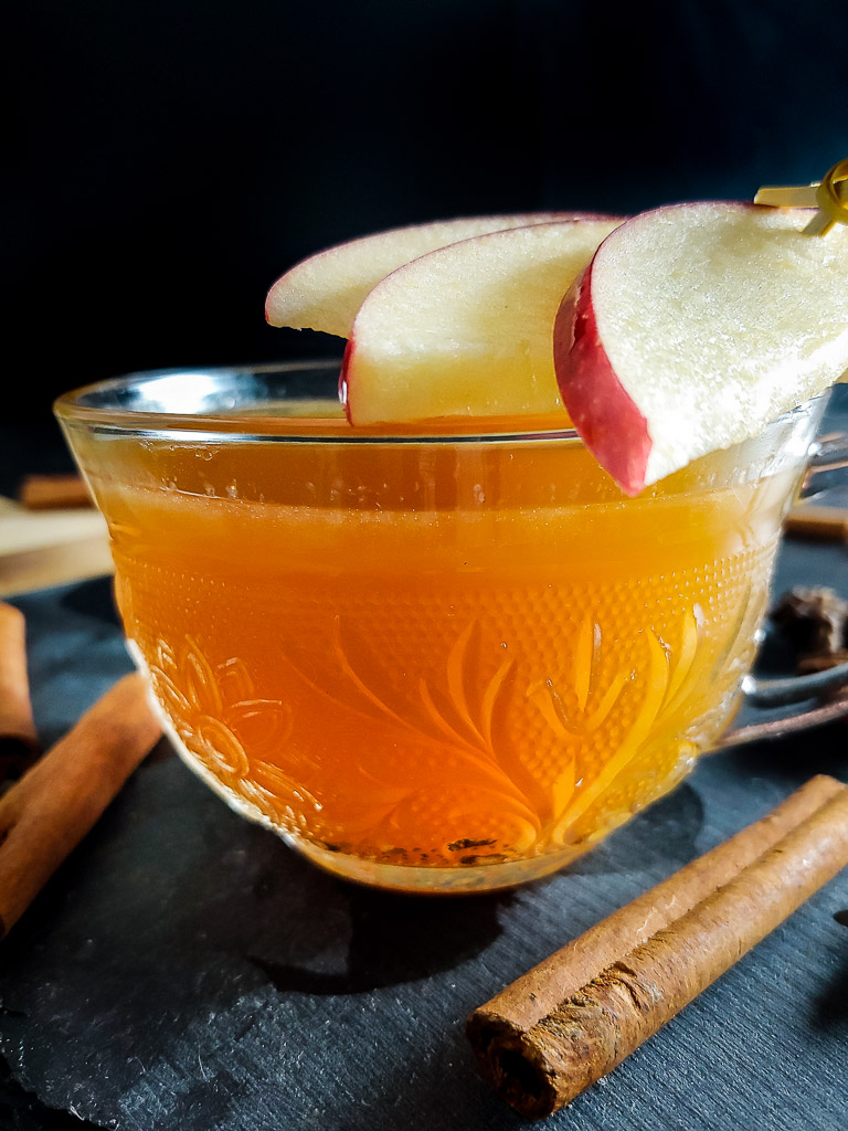 hot apple cider cocktail with apple and cinnamon garnish