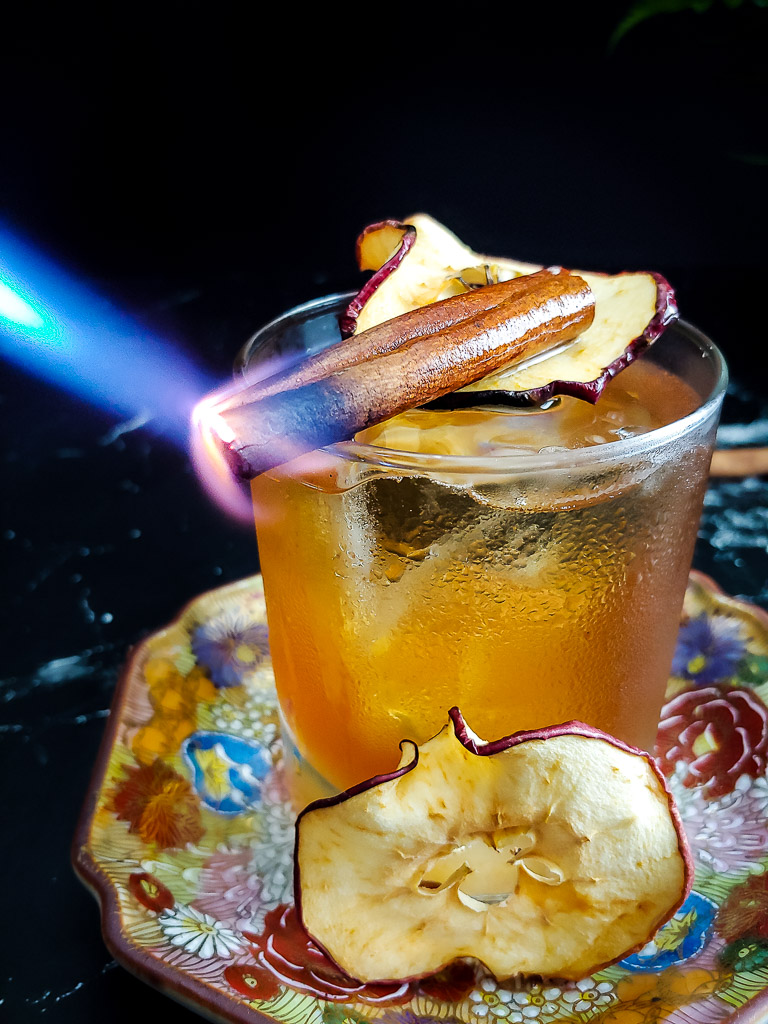 Cynar Old Fashioned with apple garnish and burnt cinnamon stick