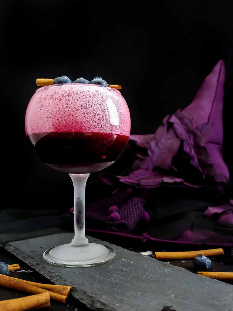 Blueberry Sour with cinnamon stick and blueberry garnish in tall, round goblet