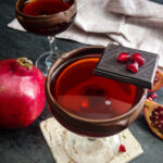 Chocolate Pomegranate Manhattan in a coupe with chocolate rim and pomegranate garnish