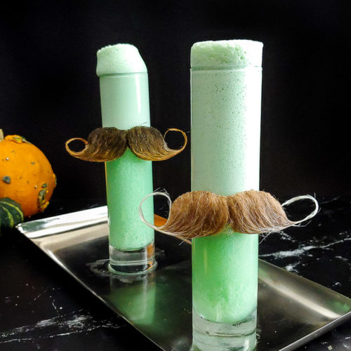 Halloween Ramos Fizz, green with moustaches on the glasses