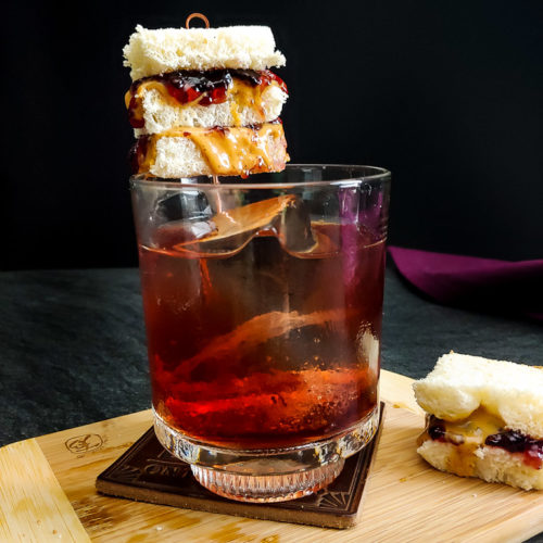 Peanut butter and jelly old fashioned with tiny pbj sandwich garnish