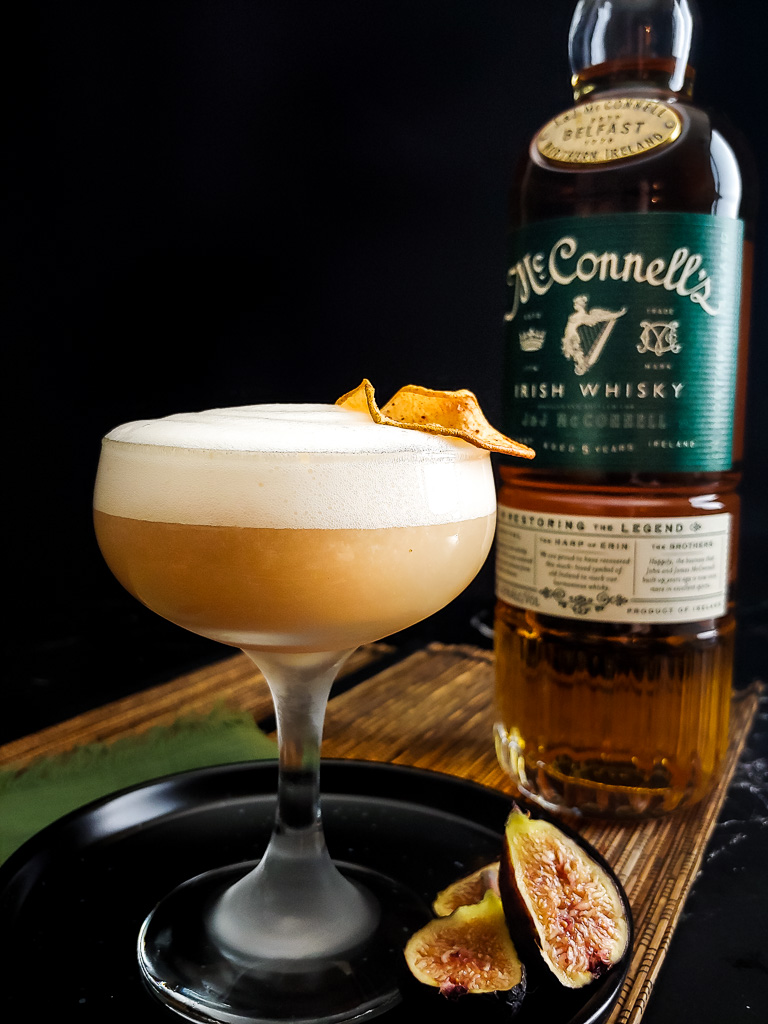 Fig and Pear Whiskey Sour with foam, McConnell's whisky bottled and dried pear garnish