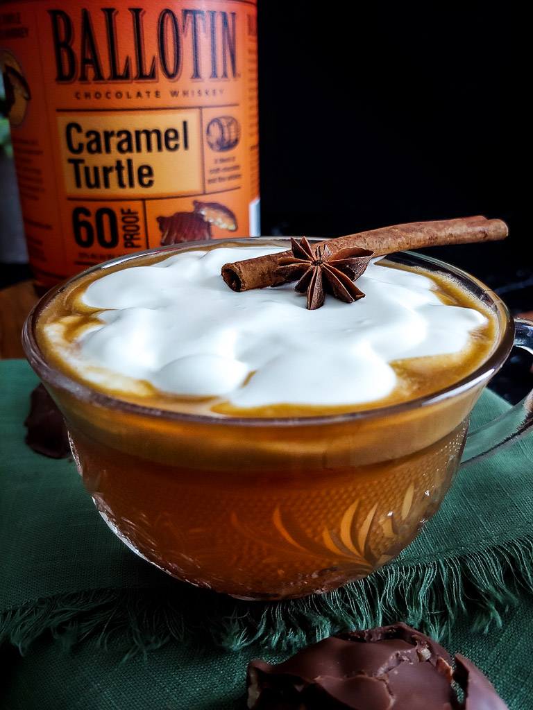 Hot Buttered Rum Cider with cinnamon stick and anise on a bed of whipped cream