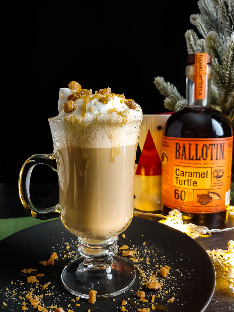 Boozy Caramel Brulee Latte topped with whipped cream, caramel drizzle and toffee with Ballotin Caramel Turtle whiskey bottle