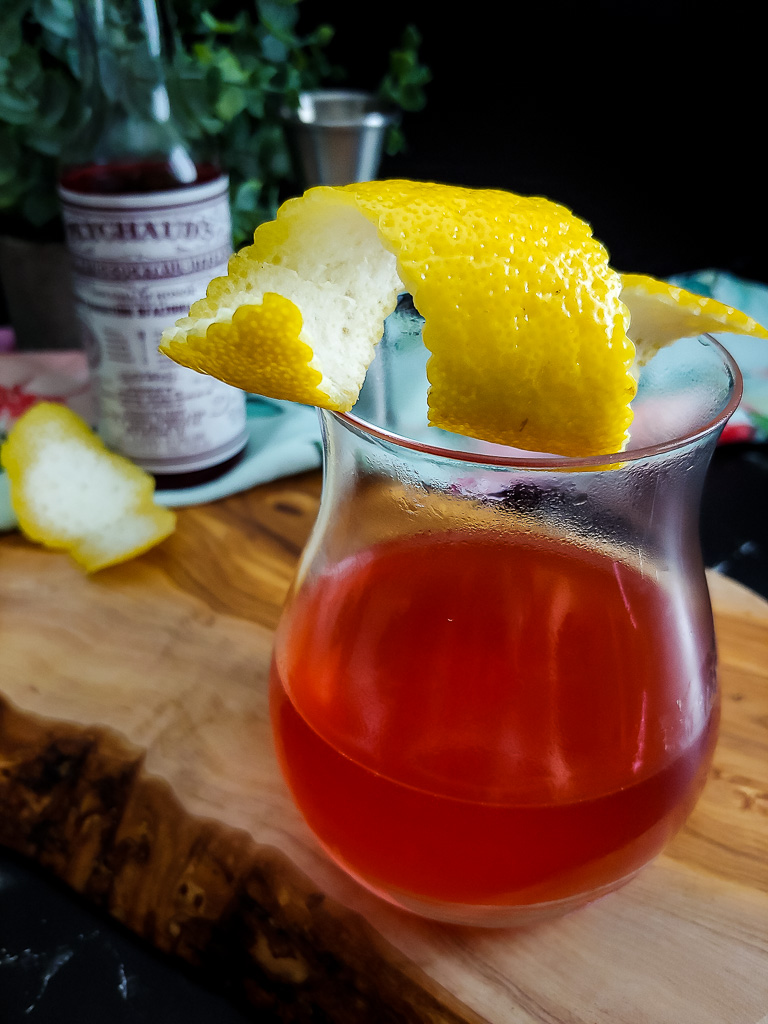 Sazerac cocktail with lemon garnish and Peychaud's bitters