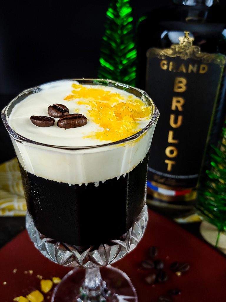Coffee Butterscotch Martini in a coupe glass with cream layer and butterscotch crumble garnish