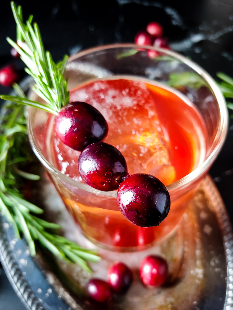 cranberry old fashioned with cranberry and rosemary sprig garnish