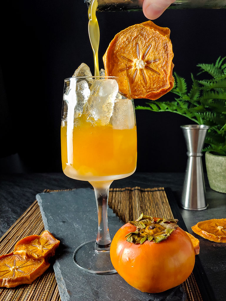 Persimmon Bourbon Cocktail pouring cocktail in tall glass from shaker tin