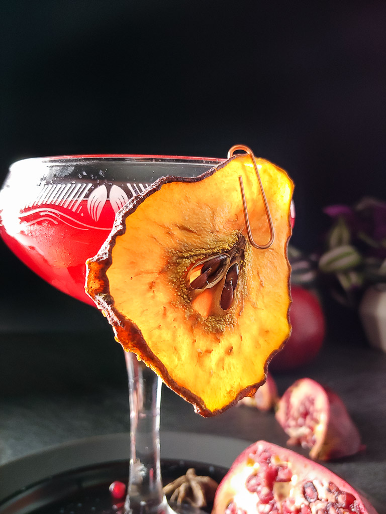 Pomegranate Brandy Sour in a coupe glass with a dried pear garnish