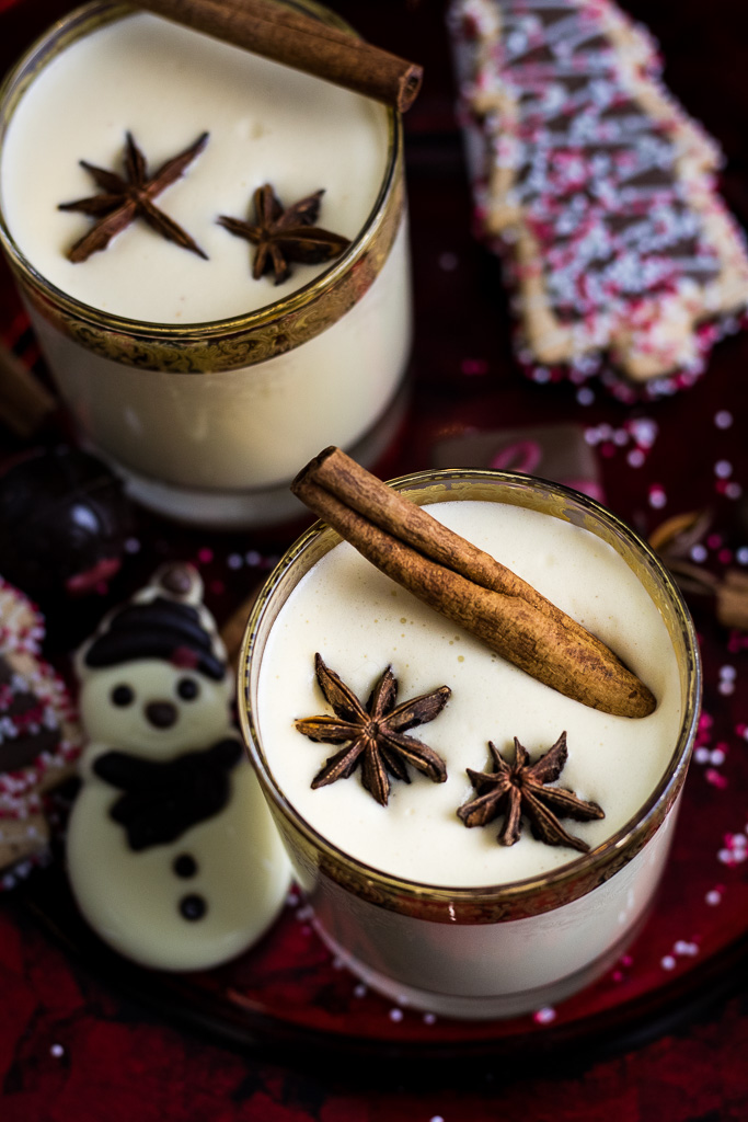 Bourbon Eggnog on a cookie and candy plate in gold rimmed glasses garnished with star anise and cinnamon