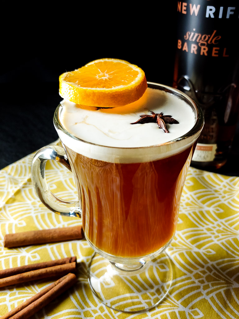 Bourbon and beer toddy in a clear mug with a cream float and orange wheel garnish