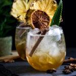 chai highball with cinnamon stick, pineapple, orange and pineapple frond garnish