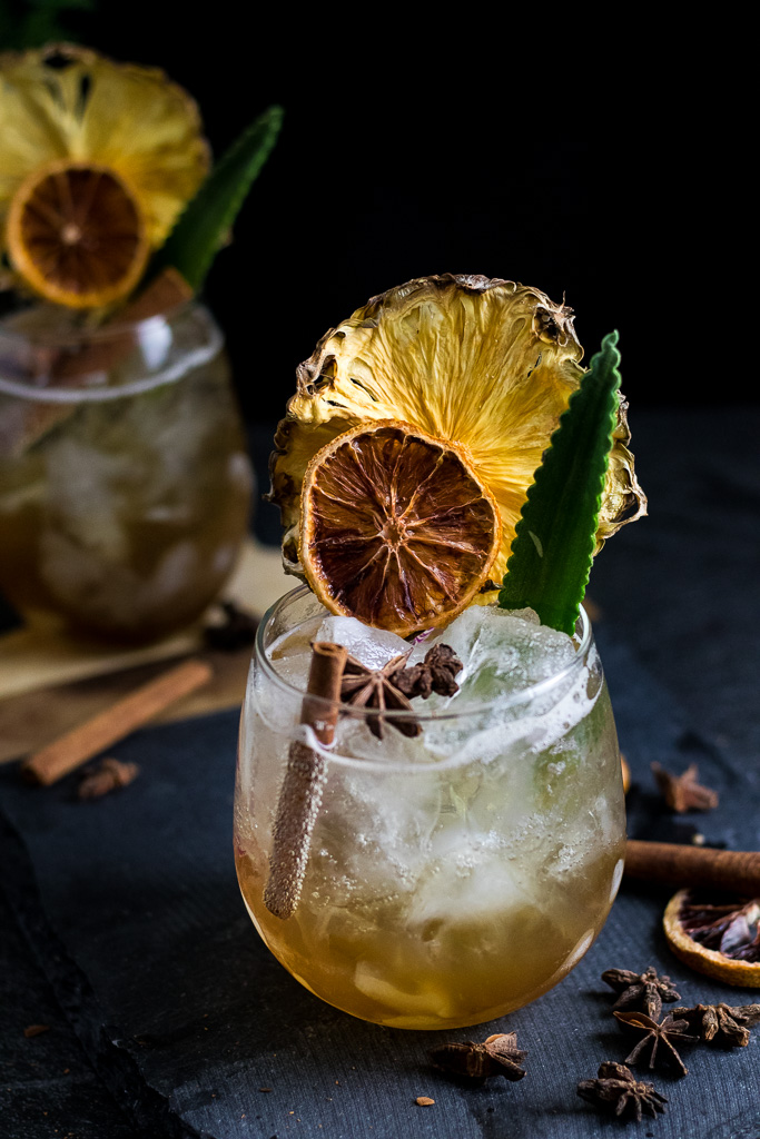 chai highball with cinnamon stick, pineapple, orange and pineapple frond garnish