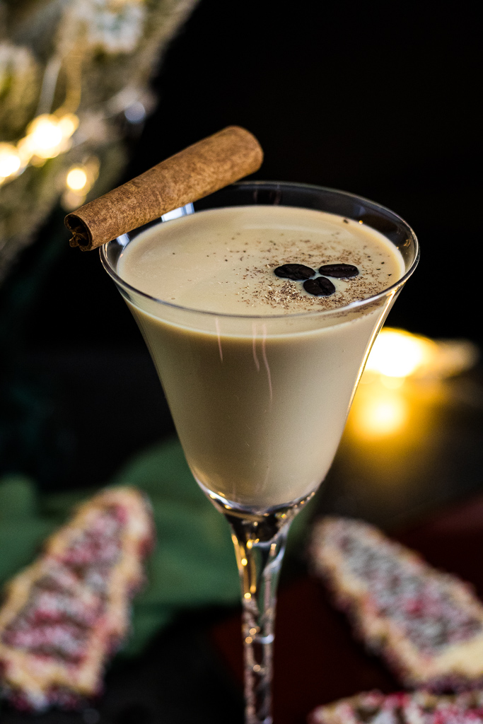 Eggnog Espresso Martini with cinnamon stick, fresh nutmeg and coffee beans in a tall martini glass