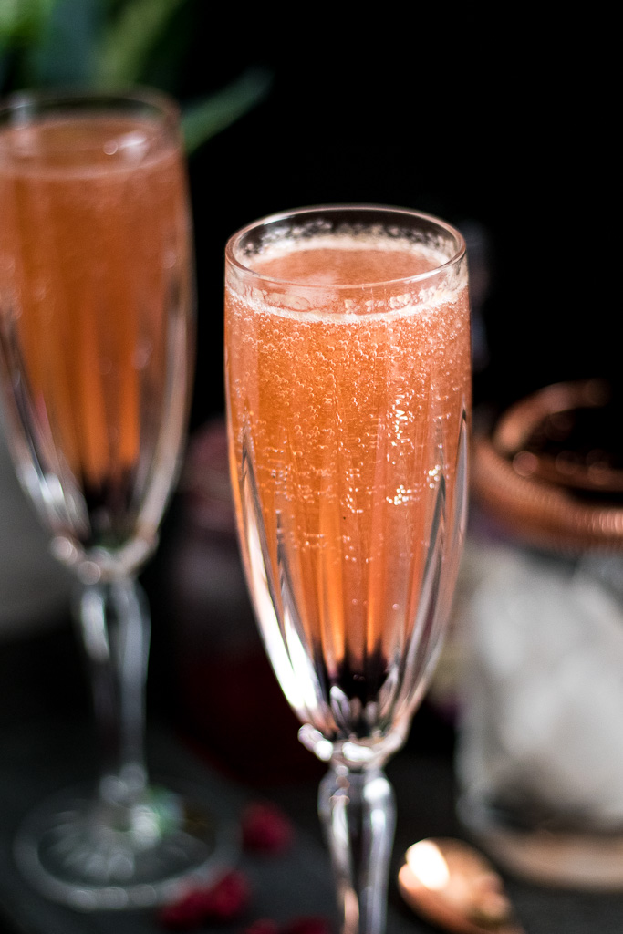 Raspberry Champagne Bubbles Cocktail in champagne flutes with copper-plated barware set and raspberry syrup and bitters