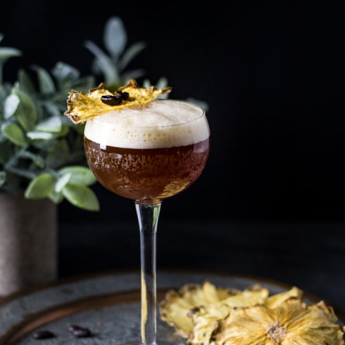 Carajillo in a tall coupe with dried pineapple slice and coffee beans