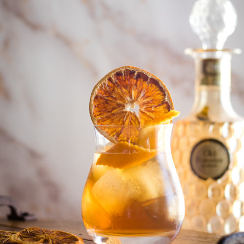 Earl Grey Cocktail with orange wheel and orange twist in ice-filled rocks glass