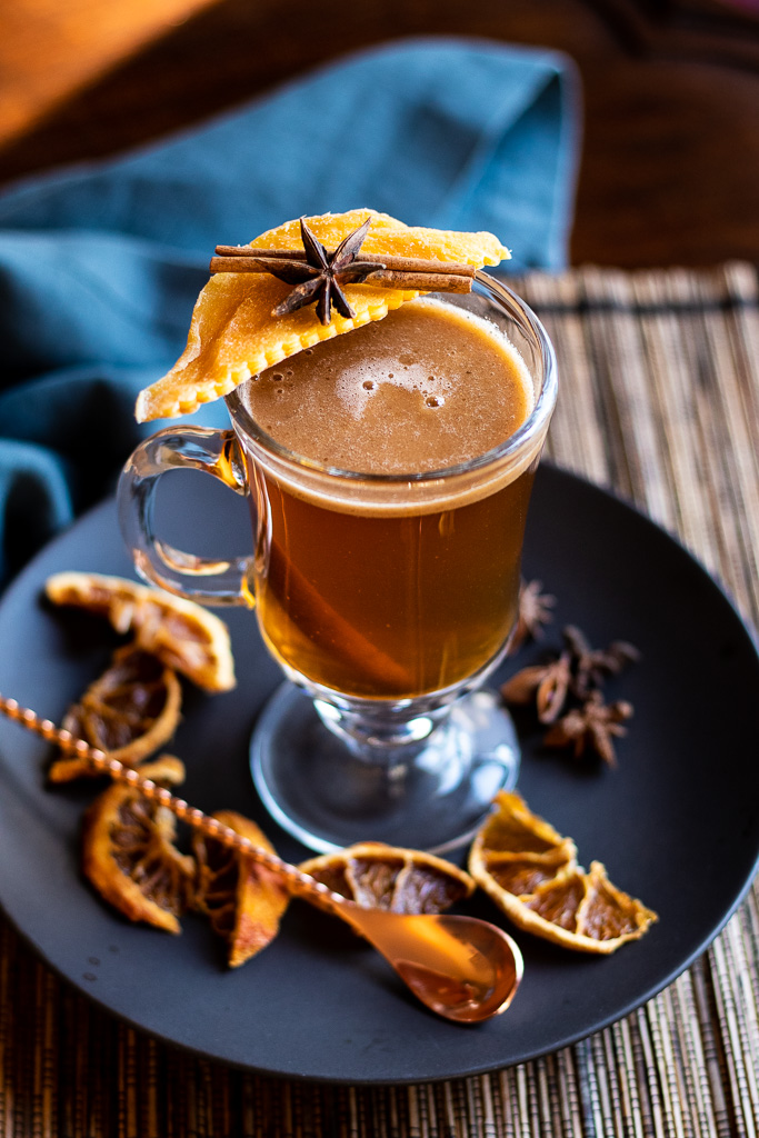 Indian Hot Buttered Rum - Kamala's Birthright - in a clear mug garnished with mango, cinnamon stick and star anise