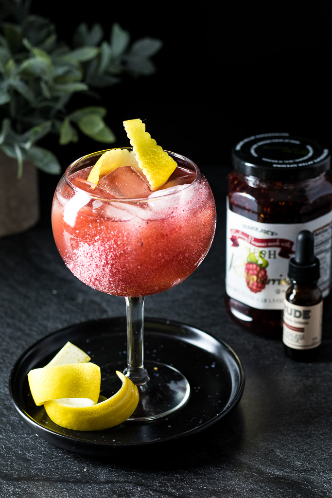 Raspberry Rue Jam Cocktail in a wine glass with ice, garnished with a lemon twist
