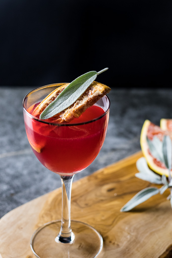 Strawberry Gin Jam Cocktail with dehydrated half wheel of grapefruit and sage leaf. Served up in a cocktail glass.