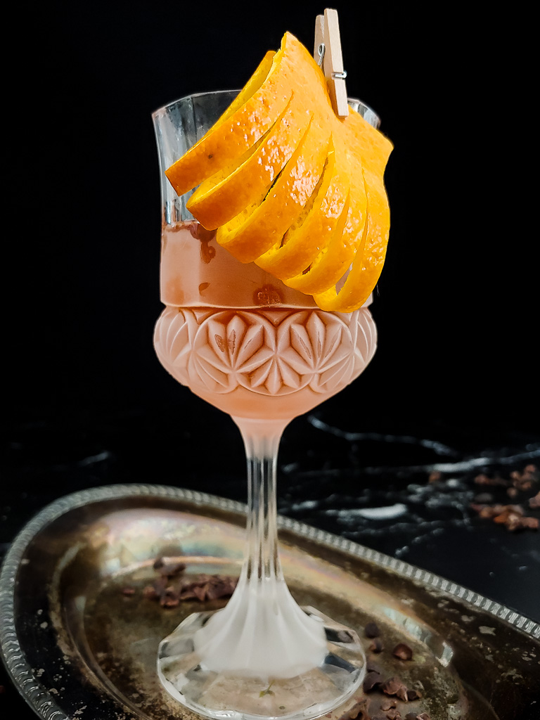 Chocolate Sazerac with rye whiskey in a frozen goblet with an orange peel and cocoa nibs