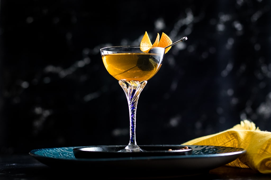 French Quarter Manhattan in a coupe glass with an orange garnish and cocktail pick with cherries