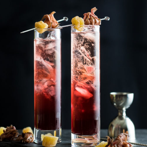 Hibiscus Highball in two glasses with hibiscus and candied ginger garnish