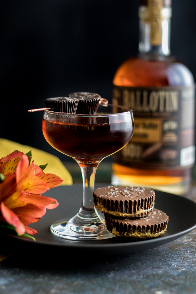 Peanut Butter Chocolate Cocktail in a coupe glass with two peanut butter cups, flowers and bottle of ballotin whiskey