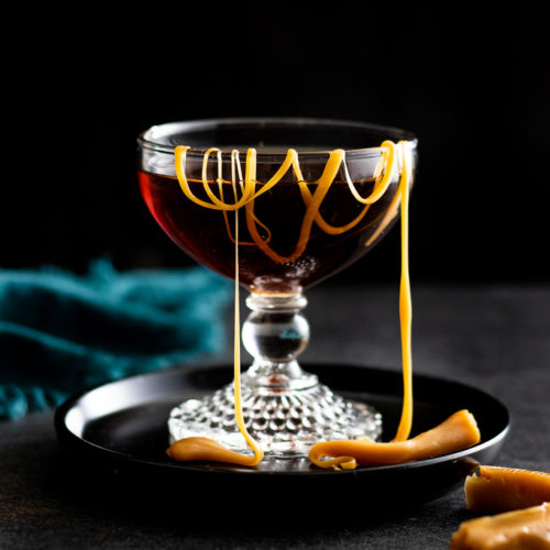 Salted Caramel Manhattan cocktail in a coupe glass with a drizzle of sea salt caramels in it