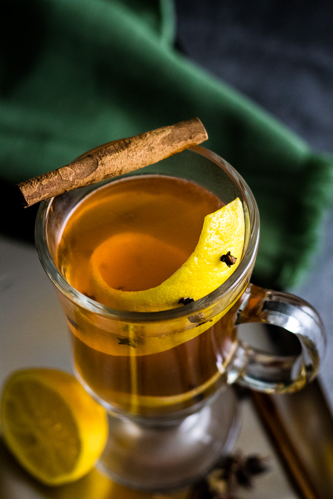 Easy Hot Toddy in a glass much with a lemon zest impaled with whole clove