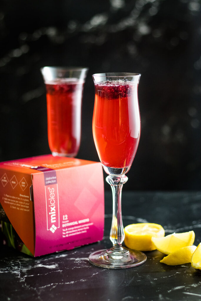 Two Ruby Bubbles cocktails in champange flutes with blackberry garnish and box of packaged Mixicles