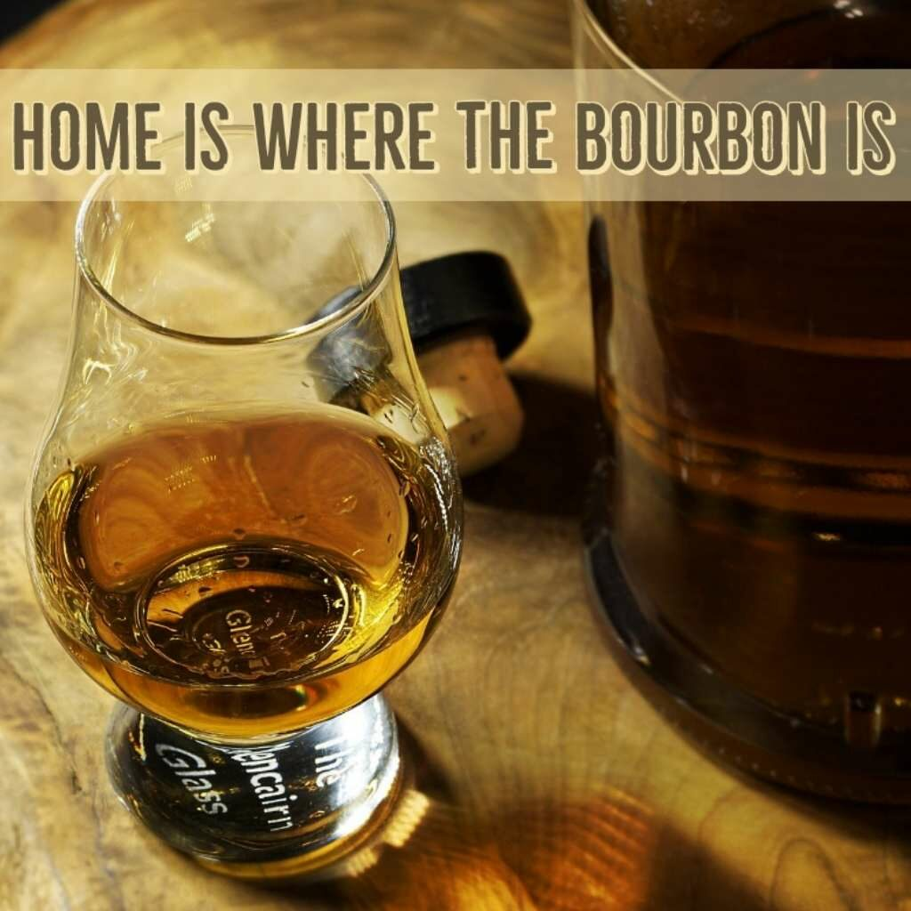 bourbon glencairn on a wood surface with Home is where the bourbon is on it.
