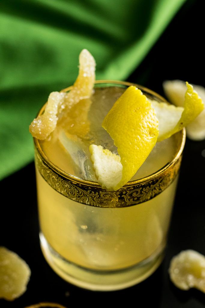 Irish Gold Rush with lemon twist and candied ginger garnish