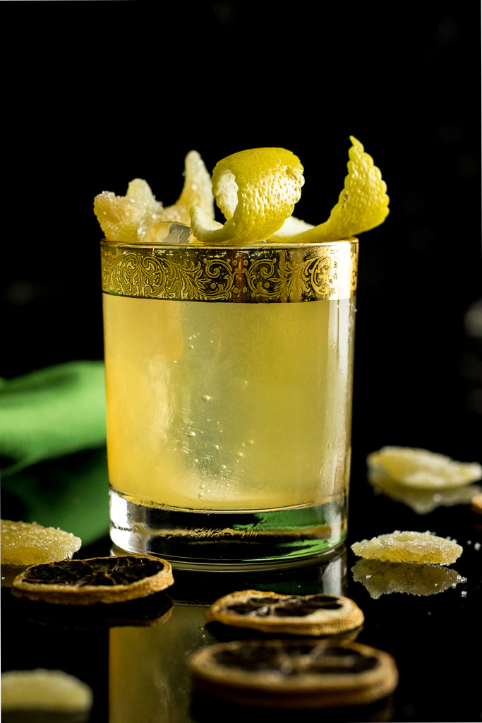 Irish Gold Rush with lemon twist and candied ginger garnish