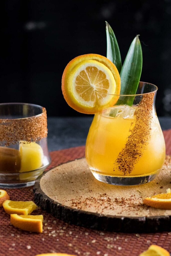 Bourbon Margarita with Mixicles garnished with orange wheel, lemon wheel, pineapple spear and chili spiced rim