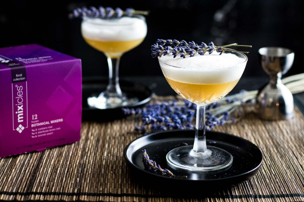 Lavender Peach Mixicles Sour with lavender garnish and box of packaged Mixicles nearby