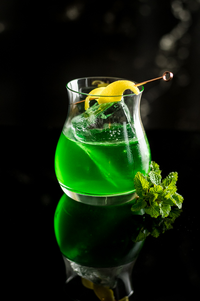 Pissed Leprechaun - Green Suze Cocktail on ice with lemon twist
