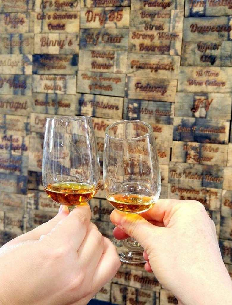 Two bourbon samples in tasting glasses as a toast