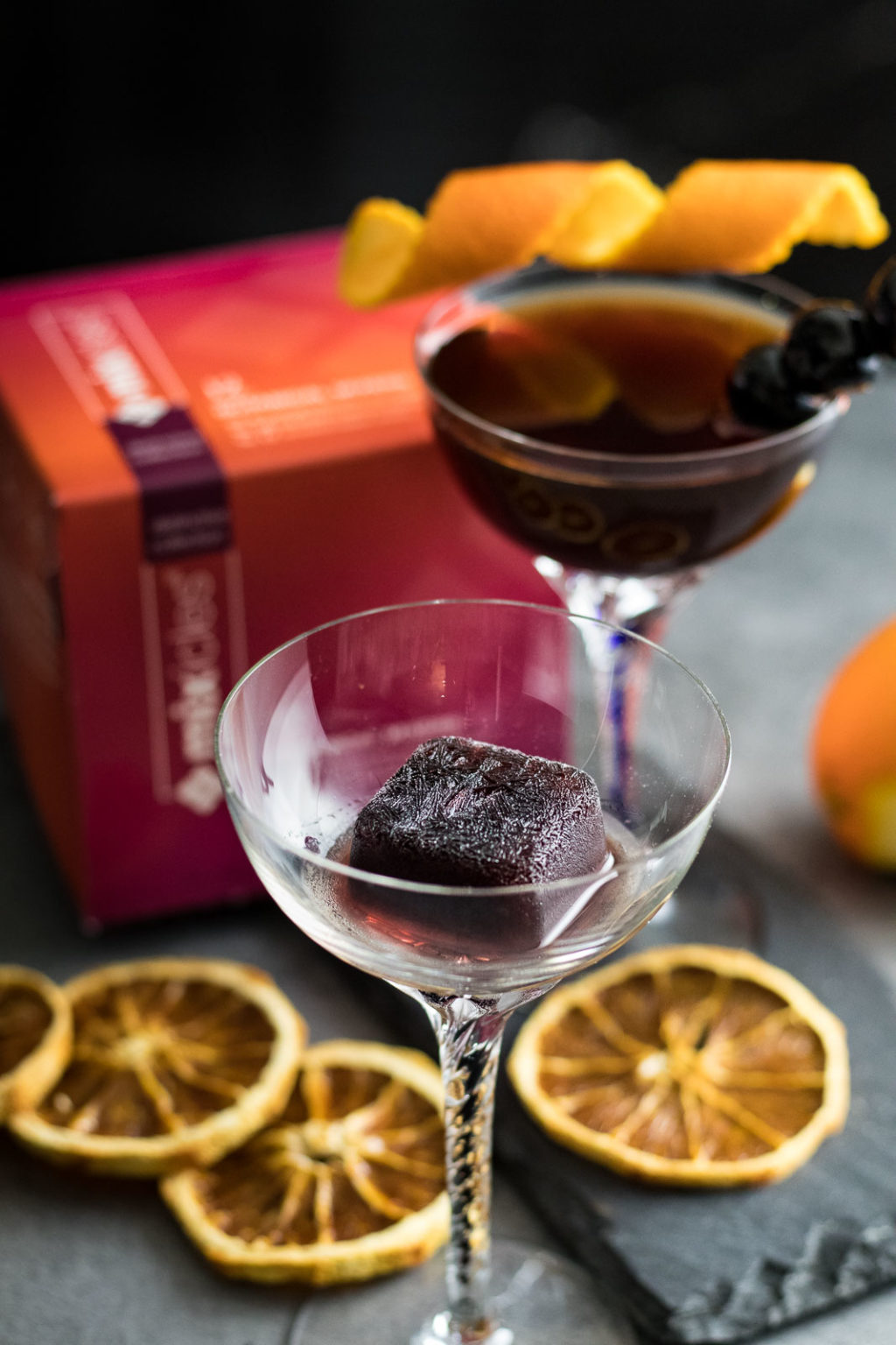 Two Smoked Cherry Manhattans with Mixcles package box nearby, garnished with orange peel