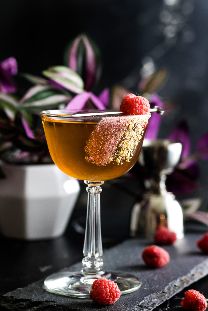 peanut butter jelly manhattan in a coupe glass with raspberry garnish and nut and crushed raspberry rim