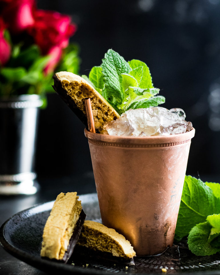 Amaretto Julep in a copper cup with mint and biscotti garnish