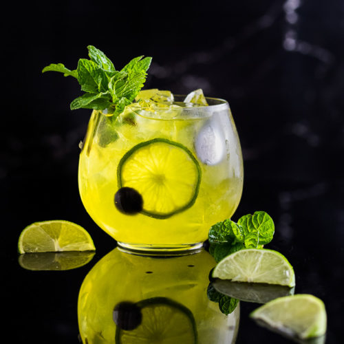 Suze cocktail - yellow mule with lime wedges and mint