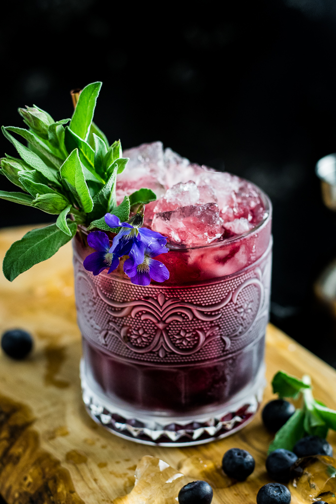Blueberry Sage Julep in a frosted rocks glass with sage garnish, blueberries and violet garnish